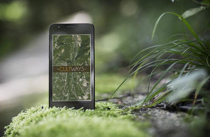 Imagen ilustrativa, teléfono con leyenda CultWays encima de una piedra con vegetación