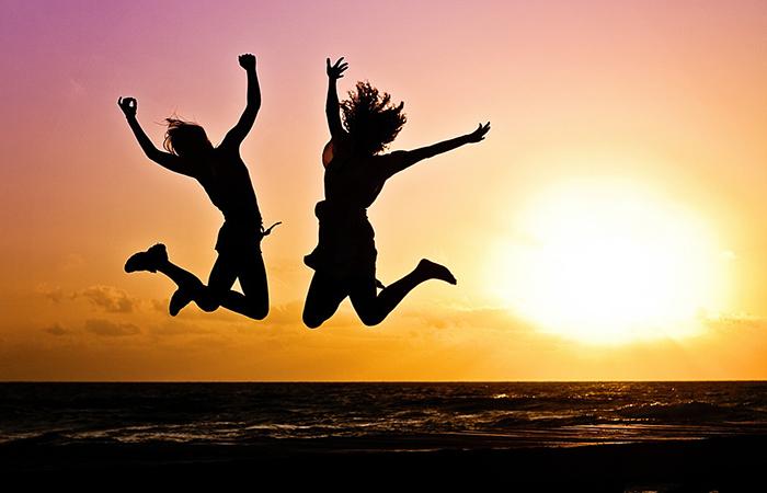 Imagen ilustrativa de dos chicas saltando de alegría